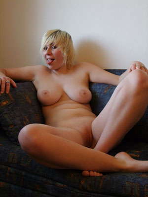 laying naked on the sofa and sticking out her tongue