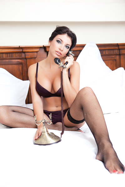brunette with massive boobs using a retro telephone to have phonesex